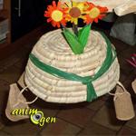 Jouet pour perroquets à fabriquer, avec un panier en dattier, des petits pots en tourbe et des liens en papier.