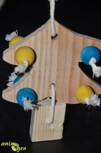 Faites de même pour lier le morceau de tasseau faisant office de tronc. Pour cacher le nœud, tirez ensuite sur la bride ainsi formée pour le cacher dans le trou. Coupez les extrémités qui dépassent.