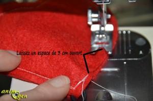 Pliez le fil en deux et épinglez-le au niveau de la pointe des cœurs, entre les deux couches de tissus. La boucle de la pliure doit dépasser à l'extérieur, tandis que les brides portant les perles restent cachées entre les deux pièces de tissus.